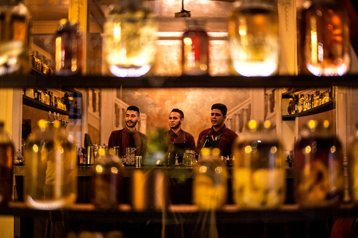 Prateleiras e baristas do Alquimico Bar em Cartagena