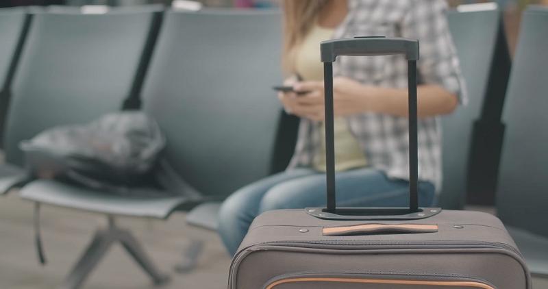 Turista aguardando voo com mala de viagem